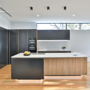 Inspiration for a large contemporary l-shaped eat-in kitchen in Sydney with an undermount sink, flat-panel cabinets, black cabinets, quartz benchtops, white splashback, stone slab splashback, black appliances, light hardwood floors, with island, white benchtop and brown floor.