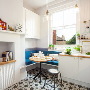 Small eclectic eat-in kitchen in London with a double-bowl sink, flat-panel cabinets, white cabinets, wood benchtops, subway tile splashback, panelled appliances, ceramic floors, no island and multi-coloured floor.