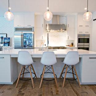 オーランドの中くらいのコンテンポラリースタイルのおしゃれなキッチン (アンダーカウンターシンク、フラットパネル扉のキャビネット、白いキャビネット、白いキッチンパネル、シルバーの調理設備、無垢フローリング、レンガのキッチンパネル) の写真