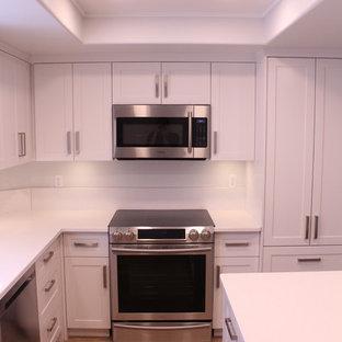 Foto di una cucina contemporanea di medie dimensioni con lavello sottopiano, ante in stile shaker, ante bianche, top in quarzo composito, paraspruzzi bianco, paraspruzzi in lastra di pietra, elettrodomestici in acciaio inossidabile, parquet chiaro, isola e pavimento beige