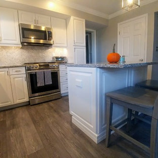 This is an example of a mid-sized transitional l-shaped eat-in kitchen in Philadelphia with an undermount sink, raised-panel cabinets, white cabinets, granite benchtops, grey splashback, mosaic tile splashback, stainless steel appliances, vinyl floors, with island, grey floor and grey benchtop.