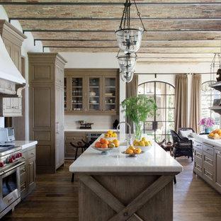 アトランタの地中海スタイルのおしゃれなアイランドキッチン (エプロンフロントシンク、レイズドパネル扉のキャビネット、茶色いキャビネット、マルチカラーのキッチンパネル、シルバーの調理設備の、茶色い床、白いキッチンカウンター、無垢フローリング) の写真