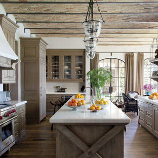 Mediterranean kitchen pictures - Kitchen - mediterranean brown floor and medium tone wood floor kitchen idea in Atlanta with a farmhouse sink, raised-panel cabinets, brown cabinets, multicolored backsplash, stainless steel appliances, an island and white countertops