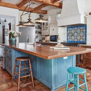Идея дизайна: большая п-образная, отдельная кухня в средиземноморском стиле с фасадами в стиле шейкер, синими фасадами, деревянной столешницей, разноцветным фартуком, техникой из нержавеющей стали, островом, раковиной в стиле кантри, полом из терракотовой плитки и коричневой столешницей