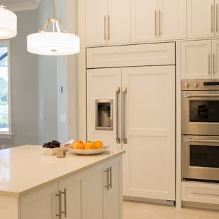 Large beach style l-shaped open plan kitchen in Miami with an undermount sink, recessed-panel cabinets, white cabinets, quartz benchtops, beige splashback, matchstick tile splashback, stainless steel appliances, ceramic floors, with island and beige floor.