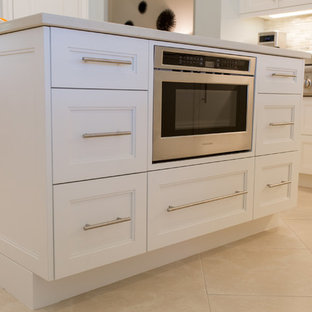 This is an example of a large beach style l-shaped open plan kitchen in Miami with an undermount sink, recessed-panel cabinets, white cabinets, quartz benchtops, beige splashback, matchstick tile splashback, stainless steel appliances, ceramic floors, with island and beige floor.