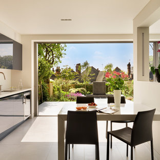 Inspiration for a medium sized contemporary l-shaped kitchen/diner in London with flat-panel cabinets, blue cabinets, composite countertops, no island, white worktops, a submerged sink, white splashback and white floors.