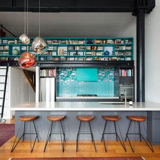 Idéer för ett mellanstort industriellt kök, med en undermonterad diskho, släta luckor, grå skåp, bänkskiva i kvarts, blått stänkskydd, stänkskydd i keramik, rostfria vitvaror och mellanmörkt trägolv