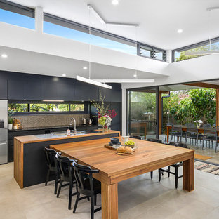 Inspiration for a contemporary galley eat-in kitchen in Sydney with flat-panel cabinets, black cabinets, wood benchtops, grey splashback, stainless steel appliances, with island, beige floor and brown benchtop.