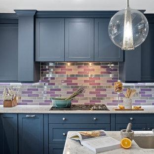 ニューヨークの巨大なエクレクティックスタイルのおしゃれなキッチン (シングルシンク、フラットパネル扉のキャビネット、青いキャビネット、大理石カウンター、マルチカラーのキッチンパネル、ガラスタイルのキッチンパネル、パネルと同色の調理設備、濃色無垢フローリング、茶色い床、白いキッチンカウンター) の写真