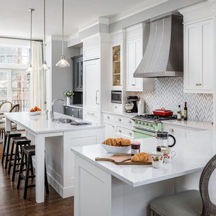 Mid-sized traditional eat-in kitchen inspiration - Example of a mid-sized classic l-shaped dark wood floor and brown floor eat-in kitchen design in Portland with an undermount sink, recessed-panel cabinets, white cabinets, paneled appliances, an island, quartzite countertops, multicolored backsplash and porcelain backsplash