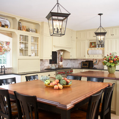 Inspiration for a timeless eat-in kitchen remodel in Boston with a farmhouse sink, shaker cabinets, yellow cabinets, wood countertops, brown backsplash, stainless steel appliances and limestone backsplash