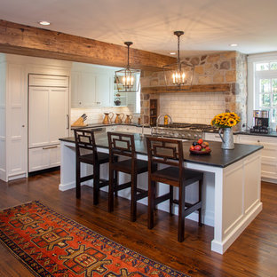 Farmhouse kitchen appliance - Inspiration for a country l-shaped dark wood floor and brown floor kitchen remodel in Philadelphia with an undermount sink, recessed-panel cabinets, white cabinets, white backsplash, subway tile backsplash, paneled appliances, an island and black countertops