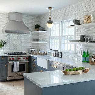 Idéer för att renovera ett mellanstort maritimt kök, med en rustik diskho, skåp i shakerstil, grå skåp, bänkskiva i kvarts, vitt stänkskydd, stänkskydd i tunnelbanekakel, rostfria vitvaror och ljust trägolv