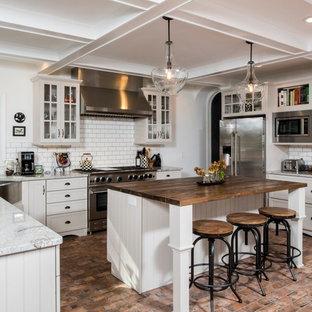 Große Landhaus Küche in U-Form mit Landhausspüle, Schrankfronten im Shaker-Stil, Granit-Arbeitsplatte, Küchenrückwand in Weiß, Rückwand aus Keramikfliesen, Küchengeräten aus Edelstahl, Backsteinboden, Kücheninsel, buntem Boden und weißen Schränken in Sonstige