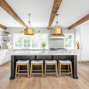 Traditional eat-in kitchen remodeling - Example of a classic l-shaped light wood floor and beige floor eat-in kitchen design in Indianapolis with an undermount sink, shaker cabinets, white cabinets, gray backsplash, subway tile backsplash, stainless steel appliances, an island and gray countertops