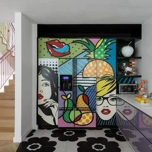 Aménagement d'une cuisine éclectique en L avec un évier intégré, un placard à porte plane, des portes de placard violettes, une crédence blanche, un électroménager de couleur, un sol multicolore et un plan de travail blanc.