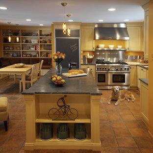 デトロイトの中サイズの地中海スタイルのおしゃれなキッチン (黄色いキャビネット、ソープストーンカウンター、シェーカースタイル扉のキャビネット、パネルと同色の調理設備、テラコッタタイルの床) の写真