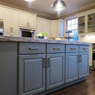 Inspiration for a large transitional u-shaped eat-in kitchen in Columbus with a farmhouse sink, raised-panel cabinets, white cabinets, recycled glass benchtops, white splashback, marble splashback, stainless steel appliances, dark hardwood floors, with island and brown floor.