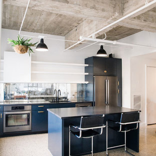 This is an example of a mid-sized industrial single-wall eat-in kitchen in Austin with an undermount sink, flat-panel cabinets, blue cabinets, granite benchtops, mirror splashback, black appliances, with island and black benchtop.