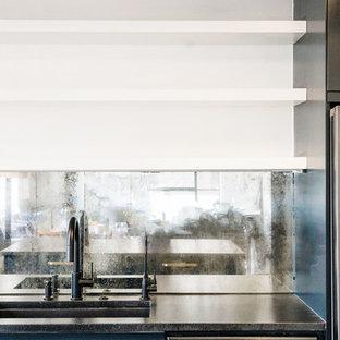 Medium sized urban single-wall kitchen/diner in Austin with a submerged sink, flat-panel cabinets, blue cabinets, granite worktops, mirror splashback, black appliances, an island and black worktops.