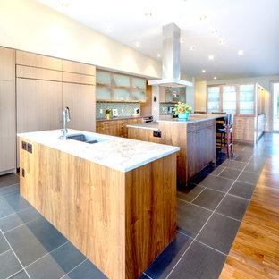 Modelo de cocina actual con fregadero bajoencimera, armarios con paneles lisos, puertas de armario de madera clara, salpicadero gris, salpicadero de azulejos tipo metro y electrodomésticos con paneles