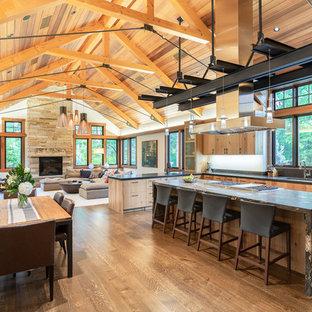 Idées déco pour une cuisine ouverte montagne avec un placard à porte plane, des portes de placard en bois brun, un électroménager en acier inoxydable, un sol en bois brun, un îlot central, un sol marron et un plan de travail gris.
