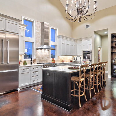 Large transitional galley concrete floor open concept kitchen photo in Austin with shaker cabinets, white cabinets, stainless steel appliances, an undermount sink, quartz countertops, beige backsplash and limestone backsplash