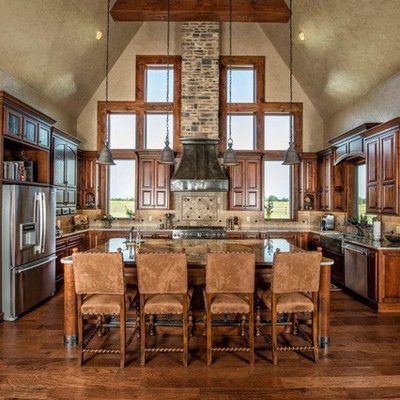Eat-in kitchen - large rustic u-shaped dark wood floor eat-in kitchen idea in Other with stainless steel appliances, a farmhouse sink, raised-panel cabinets, dark wood cabinets, granite countertops, beige backsplash, stone tile backsplash and an island