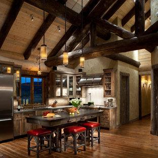 Rustik inredning av ett mellanstort l-kök, med en rustik diskho, skåp i shakerstil, skåp i slitet trä, rostfria vitvaror, mellanmörkt trägolv och en köksö