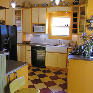 Small farmhouse enclosed kitchen designs - Small cottage l-shaped linoleum floor enclosed kitchen photo in San Francisco with a farmhouse sink, shaker cabinets, yellow cabinets, laminate countertops, white backsplash, subway tile backsplash, black appliances and a peninsula