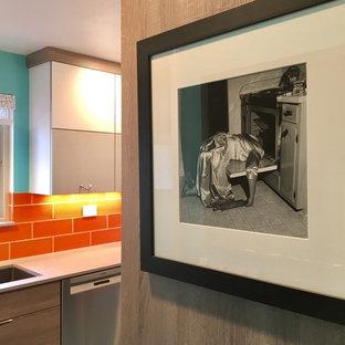 Inredning av ett 50 tals avskilt, litet parallellkök, med en enkel diskho, släta luckor, grå skåp, bänkskiva i kvarts, orange stänkskydd, stänkskydd i keramik, rostfria vitvaror, linoleumgolv och turkost golv