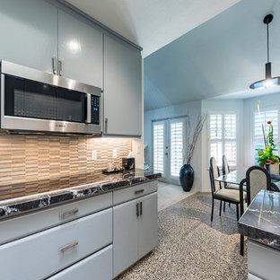 他の地域の中サイズのアジアンスタイルのおしゃれなキッチン (一体型シンク、フラットパネル扉のキャビネット、青いキャビネット、御影石カウンター、マルチカラーのキッチンパネル、ボーダータイルのキッチンパネル、シルバーの調理設備の、コルクフローリング、マルチカラーの床、黒いキッチンカウンター) の写真