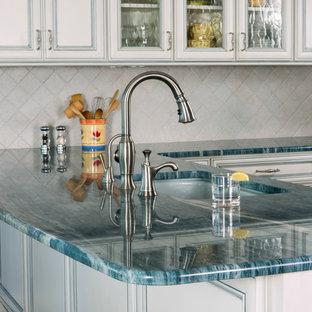 Exempel på ett mellanstort maritimt turkos turkost kök, med en undermonterad diskho, en köksö, luckor med profilerade fronter, vita skåp, marmorbänkskiva, vitt stänkskydd, stänkskydd i stenkakel, vita vitvaror och mellanmörkt trägolv