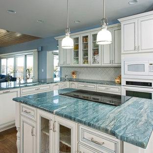 Foto på ett mellanstort maritimt turkos kök, med en undermonterad diskho, en köksö, luckor med profilerade fronter, vita skåp, marmorbänkskiva, vitt stänkskydd, stänkskydd i stenkakel, vita vitvaror och mellanmörkt trägolv