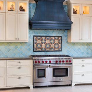 サンディエゴの大きい地中海スタイルのおしゃれなキッチン (エプロンフロントシンク、落し込みパネル扉のキャビネット、黄色いキャビネット、クオーツストーンカウンター、青いキッチンパネル、磁器タイルのキッチンパネル、シルバーの調理設備、磁器タイルの床) の写真