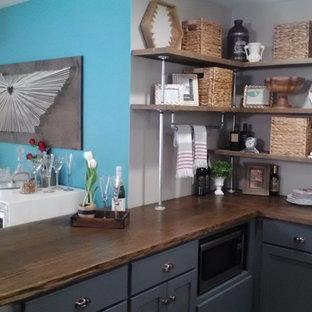ミネアポリスの中サイズのエクレクティックスタイルのおしゃれなキッチン (エプロンフロントシンク、シェーカースタイル扉のキャビネット、青いキャビネット、木材カウンター、青いキッチンパネル、ガラスタイルのキッチンパネル、シルバーの調理設備の、セラミックタイルの床) の写真