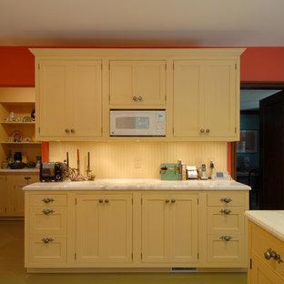Новый формат декора квартиры: отдельная, угловая кухня среднего размера в стиле фьюжн с врезной раковиной, фасадами в стиле шейкер, желтыми фасадами, мраморной столешницей, желтым фартуком, фартуком из дерева, техникой из нержавеющей стали, деревянным полом, полуостровом и бежевым полом
