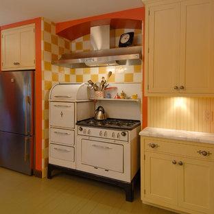 Geschlossene, Mittelgroße Eklektische Küche in L-Form mit weißen Elektrogeräten, gelben Schränken, Rückwand aus Holz, Unterbauwaschbecken, Schrankfronten im Shaker-Stil, Marmor-Arbeitsplatte, Küchenrückwand in Gelb, gebeiztem Holzboden, Halbinsel und beigem Boden in San Francisco