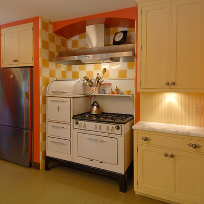 Enclosed kitchen - mid-sized eclectic l-shaped painted wood floor and beige floor enclosed kitchen idea in San Francisco with white appliances, yellow cabinets, wood backsplash, an undermount sink, shaker cabinets, marble countertops, yellow backsplash and a peninsula