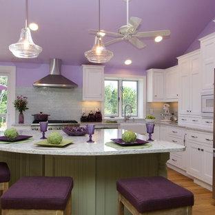 オレンジカウンティの中サイズのカントリー風おしゃれなキッチン (エプロンフロントシンク、シェーカースタイル扉のキャビネット、白いキャビネット、御影石カウンター、緑のキッチンパネル、ガラスタイルのキッチンパネル、シルバーの調理設備の、淡色無垢フローリング) の写真