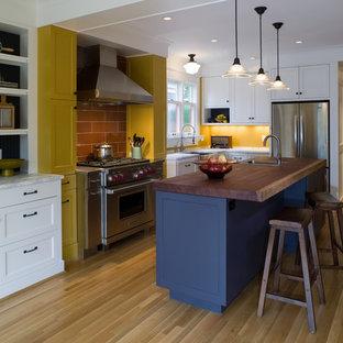 Esempio di una cucina design con elettrodomestici in acciaio inossidabile, top in legno, ante in stile shaker, ante gialle, pavimento marrone e top marrone
