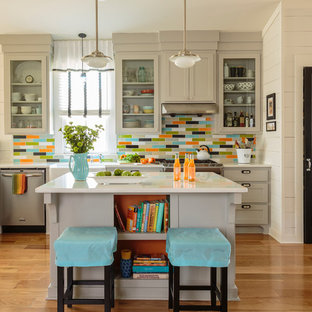 リトルロックの中サイズのカントリー風おしゃれなキッチン (エプロンフロントシンク、シェーカースタイル扉のキャビネット、グレーのキャビネット、マルチカラーのキッチンパネル、シルバーの調理設備の、無垢フローリング、クオーツストーンカウンター、セラミックタイルのキッチンパネル、白いキッチンカウンター、茶色い床) の写真