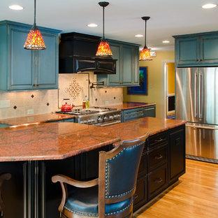 Imagen de cocina en U, tradicional, con puertas de armario con efecto envejecido, encimera de granito, salpicadero beige y electrodomésticos de acero inoxidable