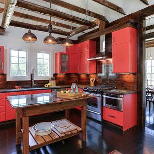 Industrial Küche in L-Form mit Unterbauwaschbecken, flächenbündigen Schrankfronten, roten Schränken, Rückwand aus Holz, Küchengeräten aus Edelstahl, dunklem Holzboden, Kücheninsel und Speckstein-Arbeitsplatte in Calgary