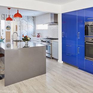 ボストンの中くらいのコンテンポラリースタイルのおしゃれなキッチン (アンダーカウンターシンク、フラットパネル扉のキャビネット、ステンレスキャビネット、クオーツストーンカウンター、白いキッチンパネル、セラミックタイルのキッチンパネル、シルバーの調理設備、クッションフロア) の写真