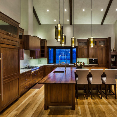 Example of a large mountain style l-shaped medium tone wood floor and brown floor open concept kitchen design in Denver with an undermount sink, shaker cabinets, dark wood cabinets, stainless steel appliances, an island, wood countertops, blue backsplash and glass tile backsplash