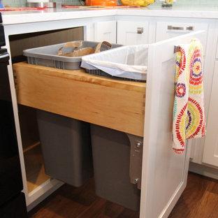 グランドラピッズの小さいエクレクティックスタイルのおしゃれなキッチン (アンダーカウンターシンク、シェーカースタイル扉のキャビネット、白いキャビネット、クオーツストーンカウンター、緑のキッチンパネル、ガラス板のキッチンパネル、黒い調理設備、磁器タイルの床) の写真