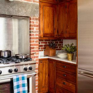 Inspiration pour une cuisine parallèle victorienne de taille moyenne avec un placard à porte shaker, un plan de travail en marbre, une crédence en brique, un électroménager en acier inoxydable, un sol en bois brun et un sol marron.