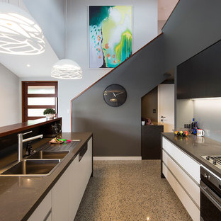 Design ideas for a mid-sized contemporary galley eat-in kitchen in Brisbane with a drop-in sink, flat-panel cabinets, white cabinets, quartz benchtops, metallic splashback, mirror splashback, black appliances, concrete floors, with island, grey floor and brown benchtop.
